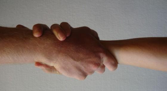 twee handen houden elkaar vast